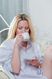 Cute girl in the bedroom with a cup of coffee Royalty Free Stock Photos