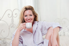 Cute girl in the bedroom with a cup of coffee Stock Photo