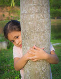 A cute girl is behind a tree Royalty Free Stock Image