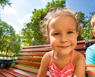 Cute girl on bench in park wide angle portrait Royalty Free Stock Image