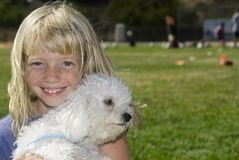 Cute Girl with Best friend. Beautiful grinning girl holding her Malti-Poo (Maltese and Poodle mix) puppy in a soccer field on a summer day Stock Photo