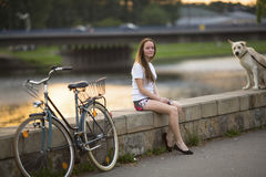 Cute girl with a bicycle and a dog sitting on the promenade in the soft sunset light. Stock Image