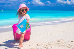 Cute girl with big luggage on white beach Royalty Free Stock Images