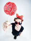 Cute girl with a big red lollipop and funny sunglasses Royalty Free Stock Image