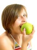 Cute girl biting a green apple Stock Photo