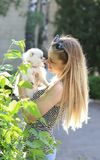 Cute girl with blond hair holds small breed dog in her arms and rejoices in the animal. Small white dog. Pomeranian. German Spitz toy royalty free stock photo