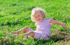 Cute girl with blond hair playing on green lawn. Cute little girl with blond curly hair playing jn green lawn with hay heap Royalty Free Stock Image