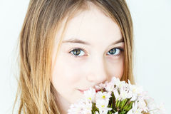 Cute girl with blond long hair. Close portrait of girl eleven years old with big green eyes with white flowers royalty free stock photos