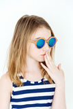 Cute girl with blond long hair. Cute girl eleven years old in green sunglasses on white royalty free stock images