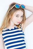 Cute girl with blond long hair. Cute blond girl eleven years old standing near white wall with green sunglasses royalty free stock images