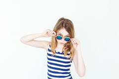 Cute girl with blond long hair. Laughing blond girl in green sunglasses on white royalty free stock photo