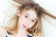 Cute girl with blond long hair. Portrait of girl eleven years old with big eyes playing with long hair stock photo