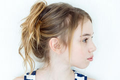 Cute girl with blond long hair in profile. Cute girl eleven years old with blond long hair on white wall background in profile royalty free stock images