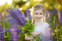 Cute girl in blooming lupine field Stock Image