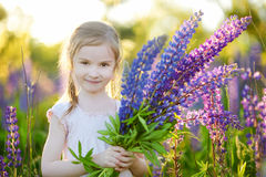 Cute girl in blooming lupine field Royalty Free Stock Photo
