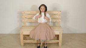 Cute girl in a blouse and black hat, she poses in the Studio with a white wall. Cute little girl in vintage clothes sitting on a wooden eco-bench in a white stock video