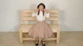 Cute girl in a blouse and black hat, she poses in the studio with a white wall. Cute little girl in vintage clothes sitting on a wooden eco-bench in a white stock video footage
