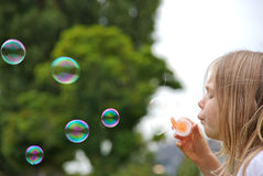 Cute girl blowing bubbles Royalty Free Stock Images