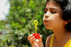 Cute girl blowing bubbles Stock Photography