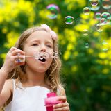 Cute girl blowing bubbles oudoors. Stock Image