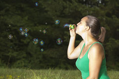 Cute girl blowing colorful bubbles Stock Image