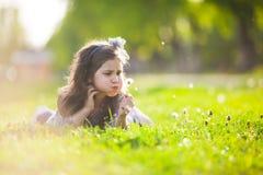 Cute girl blowing dandelion Stock Image