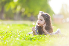 Cute girl blowing dandelion Stock Photo
