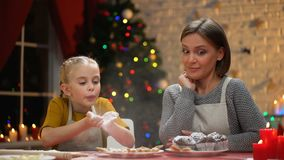 Cute girl blowing on flour mother looking at her, having fun on Christmas eve. Stock footage stock video