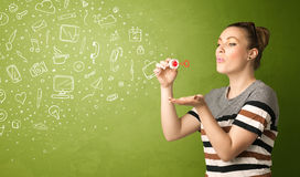 Cute girl blowing hand drawn media icons and symbols Royalty Free Stock Image
