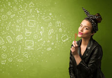 Cute girl blowing hand drawn media icons and symbols Royalty Free Stock Photography