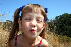 Cute girl blowing kiss. Portrait of cute girl blowing kiss and pulling funny face in countryside Royalty Free Stock Photography