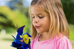 Cute girl blowing pinwheel at park Stock Photos
