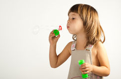 Cute girl blowing soap bubbles Stock Images