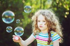 Cute girl blowing soap bubbles, closeup portrait. Stock Images
