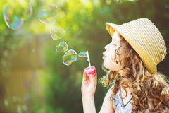 Cute girl blowing soap bubbles in a heart shape. Royalty Free Stock Image
