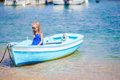 Cute girl in blue boat in the sea bay near the town of Mykonos in Greece. Little kid enjoy swimming in the small boat. Stock Photography