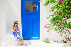 Cute girl in blue dress at street of typical greek traditional village with white walls and colorful doors on Mykonos Stock Photos
