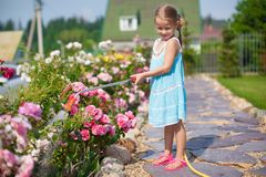 Cute girl in blue dress watering flowers with a Stock Images
