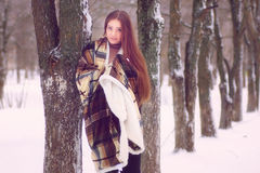Cute girl with blue eyes wrapped in a blanket in the winter Royalty Free Stock Image