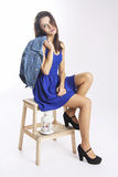Cute girl in blue jacket on wooden chair Royalty Free Stock Images