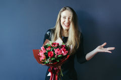 Cute girl with bouquet of red tulips. Royalty Free Stock Photos