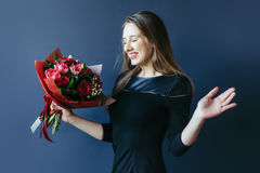 Cute girl with bouquet of red tulips. Royalty Free Stock Image