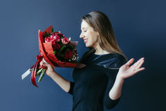 Cute girl with bouquet of red tulips. Stock Image