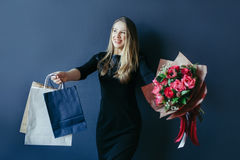 Cute girl with bouquet of red tulips and packages. Stock Photos