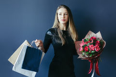 Cute girl with bouquet of red tulips and packages. Stock Photography