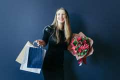 Cute girl with bouquet of red tulips and packages. Royalty Free Stock Photography