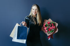 Cute girl with bouquet of red tulips and packages. Royalty Free Stock Images