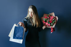Cute girl with bouquet of red tulips and packages. Stock Images