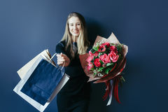 Cute girl with bouquet of red tulips and packages. Stock Photo