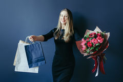 Cute girl with bouquet of red tulips and packages. Royalty Free Stock Image